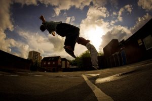 Traceurs qui pratiquent le parkour en faisant un backflip sans obstacle