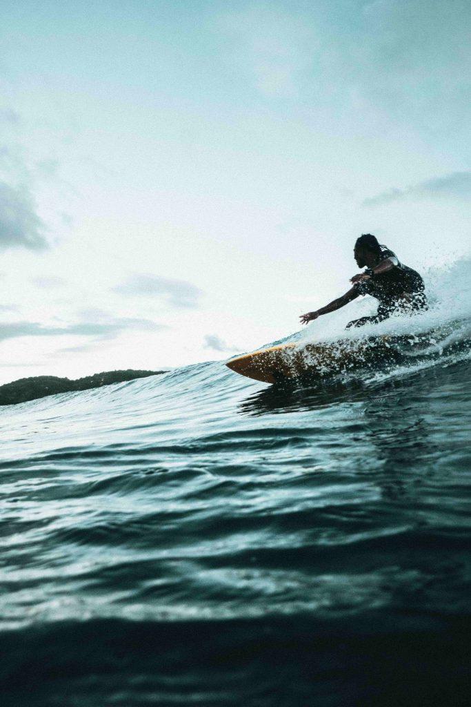 Une silhouette surfant sur une mer grise