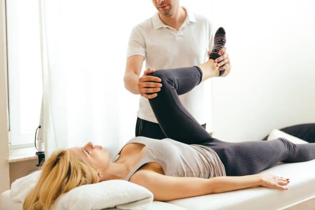 Jeune femme sportive en consultation avec un ostéopathe qui lui ausculte le genou