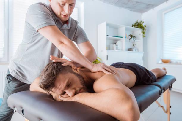 Sportif qui consulte un ostéopathe pour soulager ses douleurs dans le dos