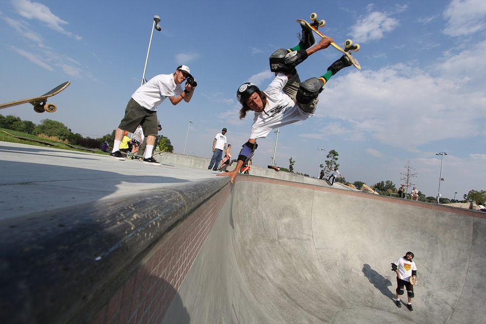 Skateur qui réalise un handplant sur son skate avec des protections